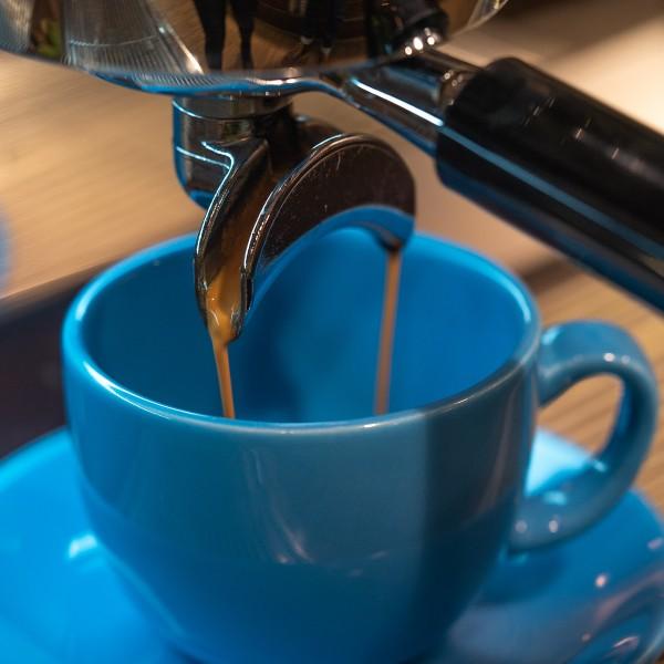 Kaffe-l-uft-in-blaue-Tasse